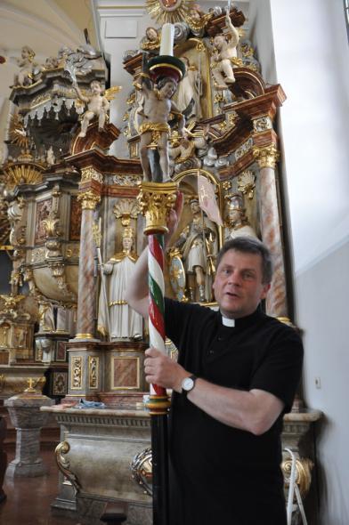 Pfarrer Matthias Kaminski hält den Schützenpfosten mit dem heiligen Sebastian